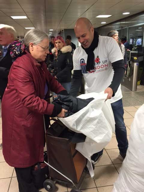 Lady donating coat to Wrap Up London