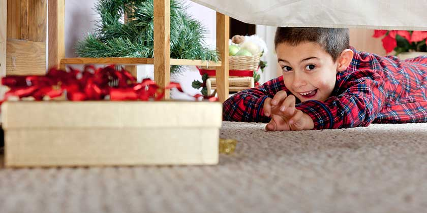 Child searching under bed for Christmas Presents